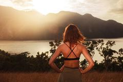 Young woman admiring sunset over bay - stock photo
