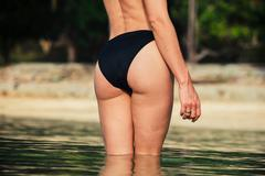 The rear of a sexy woman on tropical beach - stock photo