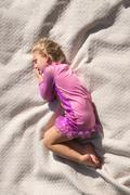 Sleeping girl curled up on a bed Stock Photos