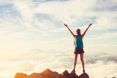 Happy Woman Hiker With Open Arms at Sunset on Mountain Peak - stock photo