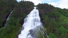 Massive waterfall in norwegian forest, aerial footage Stock Footage