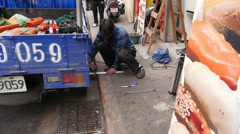 Worker men cut metal part with electric cut machine. sit on street side - stock footage