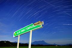 Star trails and broken road sign, Borneo, Malaysia - stock photo