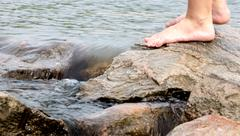 Person's feet standing on rocks at the beginning of the  Mississippi, Minnesota, Stock Photos