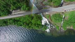 Massive Svandalsfossen waterfall creating rainbow on road bridge in Norway Stock Footage