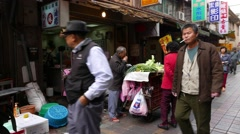 Aged hawker sell greengrocery on market street, quick look while walk aside Stock Footage
