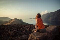 Woman sitting on unusual rock at sunrise - stock photo