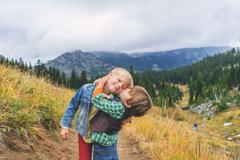 Two brothers hugging and kissing on mountain path Stock Photos