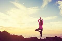 Woman Practicing Yoga in the Mountains at Sunset Stock Photos