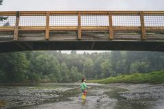 Girl playing in shallow water under bridge - stock photo
