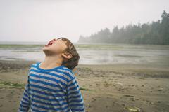 Boy with his head tilted back catching rain in mouth Stock Photos