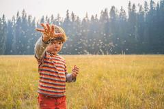 Boy throwing seeds in a field - stock photo