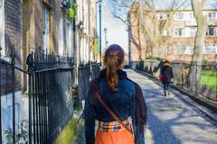Woman walking cobbled street - stock photo