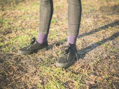 Legs oand feet of person standing on the grass - stock photo