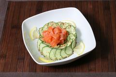 sliced red fish, sliced of lemon, cucumber, and sesame seeds - stock photo