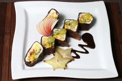 nutritious fruit dessert in the form of sushi - stock photo
