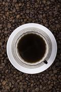 Cup of coffee against beans background closeup Stock Photos