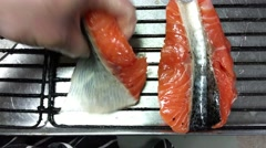 Placing salmon medallions on a broil, at a restaurant kitchen - stock footage