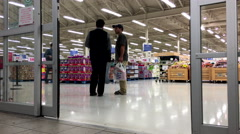 People with Shopping Cart Walking Through the Doors at superstore - stock footage