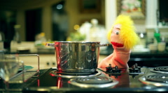 Puppet in kitchen cook look at pot Stock Footage