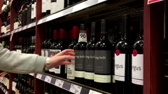 A hand takes bottles of red wine from the shelf. - stock footage