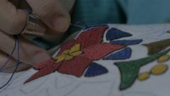 Woman embroidering flower by pattern on tablecloth or doily, extreme close up. Stock Footage
