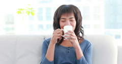 Stock Video Footage of Smiling woman drinking hot beverage