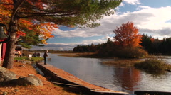 Man fishing off lake dock during Fall sunset - wide Stock Footage