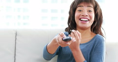 Attractive woman holding a remote sitting on the sofa Stock Footage