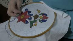 Granny embroidering flower decoration on tablecloth, close up. - stock footage