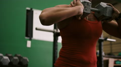A fit young woman doing lunges while holding a dumbbell in a small gym Stock Footage