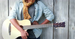 Smiling hipster woman playing guitar - stock footage