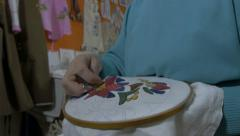 Embroidery by pattern,making traditional design on textile with needle,tilt down Stock Footage