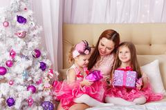 Mother of two daughters gave Christmas presents. - stock photo
