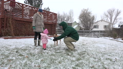 Family play in snowy winter backyard baby figuring out snow. Stock Footage