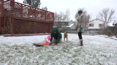 Baby's first sled ride across the flat snowy lawn during blizzard beginnings. Stock Footage