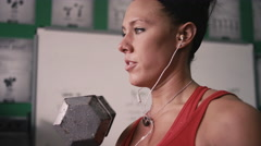 Close up of a fit young woman doing dumbbell curls in a small gym - stock footage