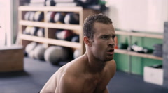 A fit young man doing squats with a kettle bell in a small gym Stock Footage