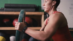 A fit young woman working out with a bumper plate in a small gym - stock footage