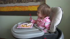 Baby girl eating at a high chair a lunch of gluten free pasta and steak. Stock Footage