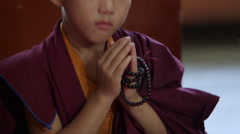 Buddhist child monk praying with prayer beads. Stock Footage