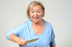 Elderly woman brandishing a kitchen knife - stock photo
