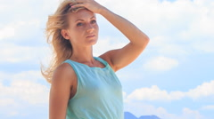 Stock Video Footage of portrait of blonde girl smoothing hair under wind