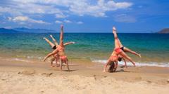 Cheerleaders in bikinis perform hand scale stunt on wet sand Stock Footage
