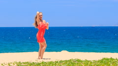 Blond girl in red dances barefoot on sand beach smooths hair Stock Footage
