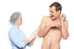 Woman doctor puts a prick. The man is afraid and feels panic. Isolated on white - stock photo