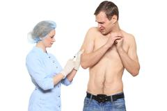 Woman doctor puts a prick. The man is afraid and feels panic. Isolated on white Stock Photos