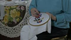 Embroidery. Woman embroidering flower decoration on tablecloth,close up,tilt up. Stock Footage