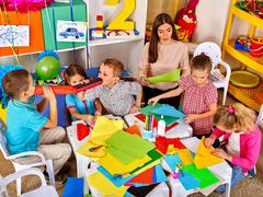 Children with teacher woman painting on paper in  kindergarten Stock Photos
