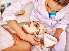 Woman middle-aged take face massage in spa salon Stock Photos